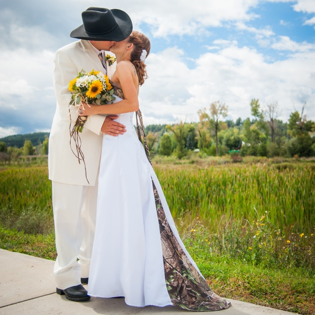 Bryan's wedding style included a light suit and cowboy hat which matched his bride's camo train.