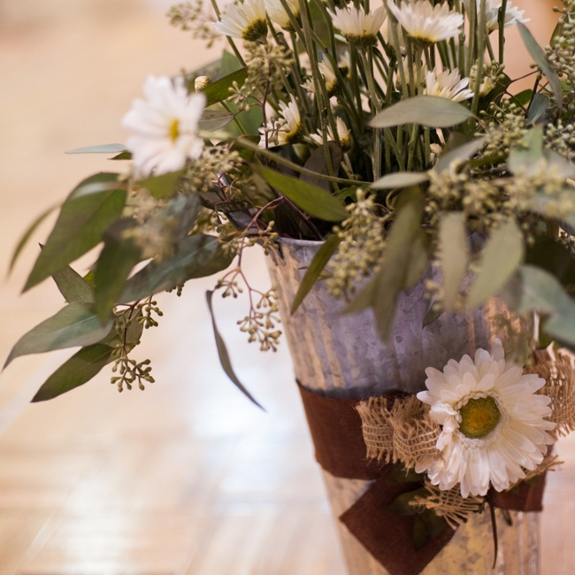 The reception featured rustic centerpieces: tin pales filled with burlap accents and filled with daisies.