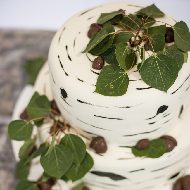 One of Tayler and Bryan's two cakes was a round cake decorated with wood texturing, chocolate acorns and real leaves.