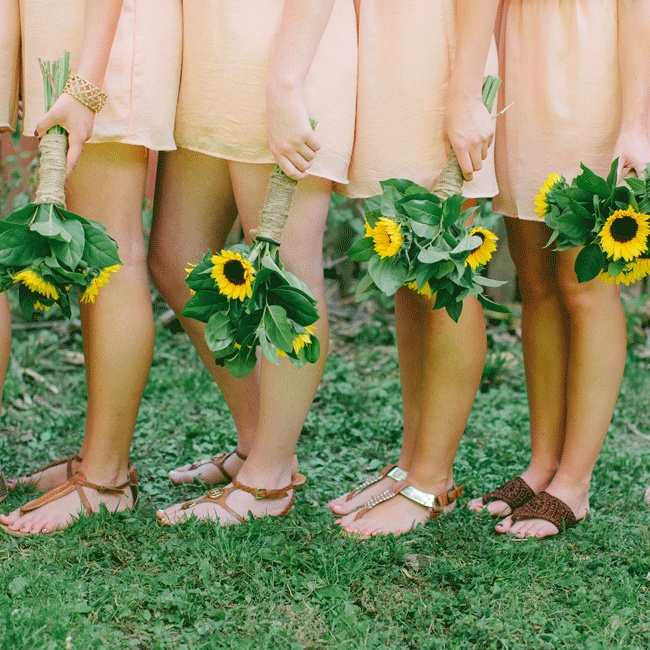 The bridesmaids wore different brown sandals and carried summery sunflower bouquets wrapped with twine.