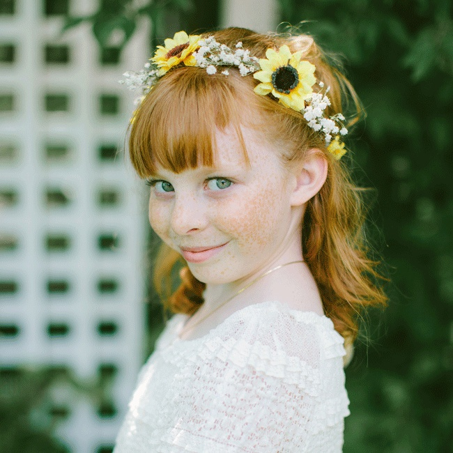 The groom's niece completed her adorable flower girl look with a sunflower and baby's breath headpiece, white lace dress and a rose petal-filled basket.