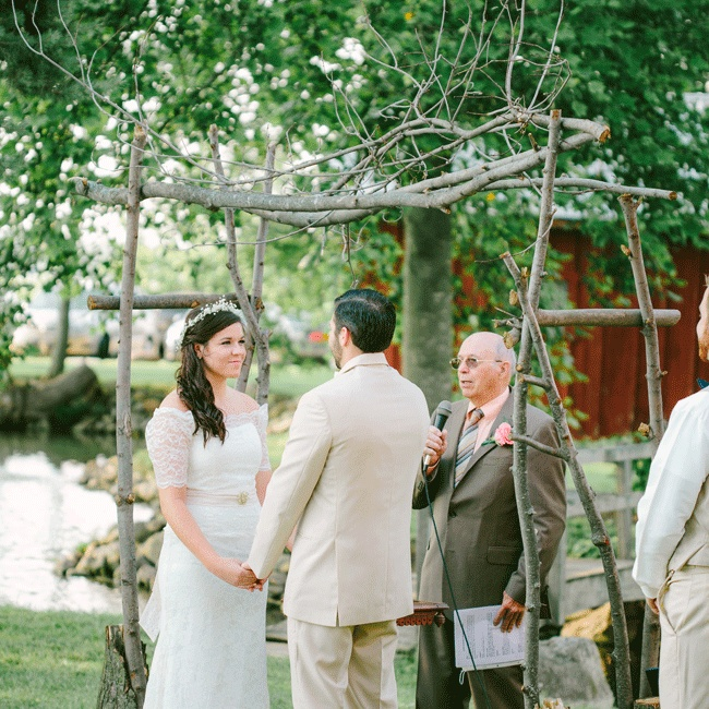 Married by the groom's grandfather, the couple exchanged vows under a rustic wooden arch during the outdoor evening ceremony.
