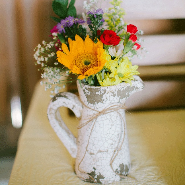 Bright daisies, sunflowers and roses popped in a vintage pitcher were accented with a twine bow.