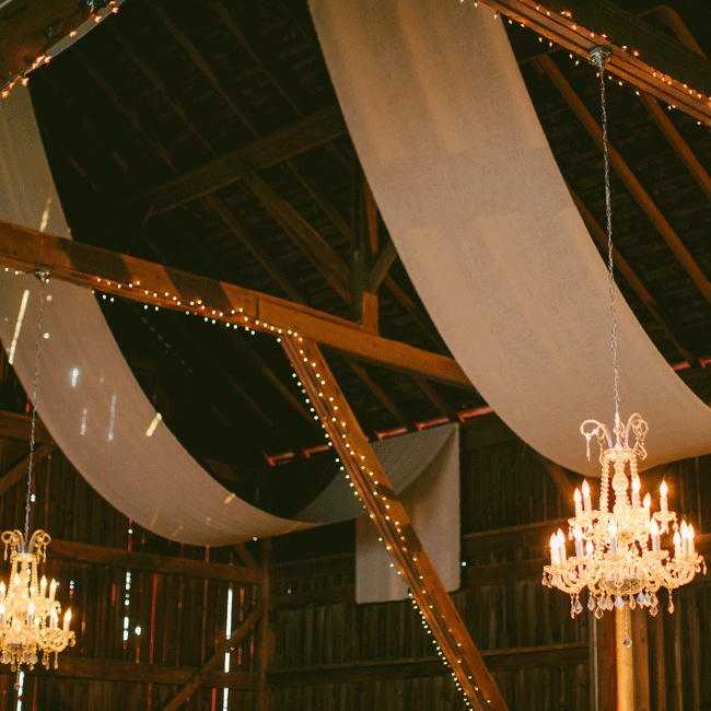 Chandeliers and sheets of ivory fabric hung from the barn's ceiling, warming the intimate reception space.