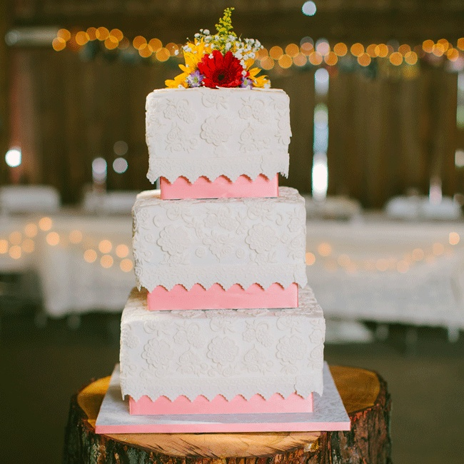 The square cake's fondant elegant lace pattern matched the bride's vintage gown and was topped with fresh daisies.