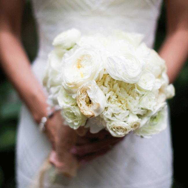 This delicate ivory gardenia, patience, peony and cabbage rose bouquet was tied with sheer gold ribbon and a piece of the bride's dress.