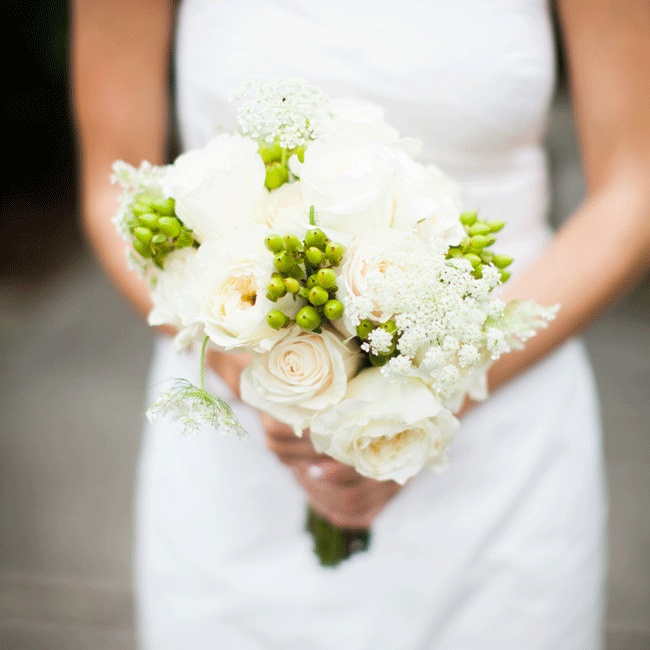 The bridesmaids carried ivory gardenia, patience and cabbage rose bouquets similar to the bride's with additional Queen Anne's lace and green berries for a hint of color.