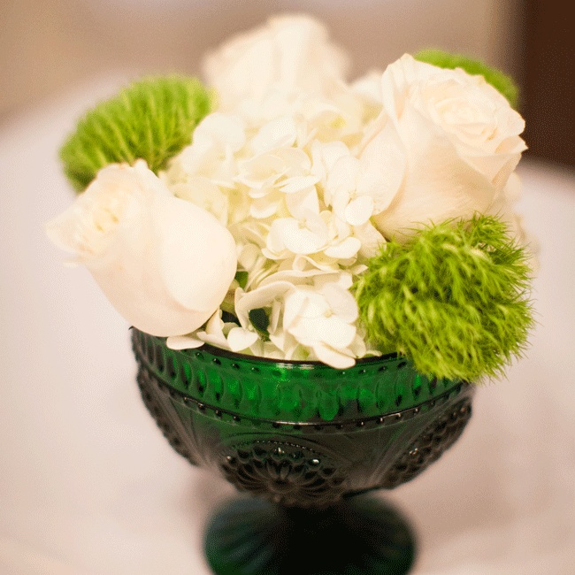 Deep green glass vases held small arrangements in the same tones as the couple's wedding colors.