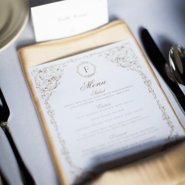 Menu cards designed and printed by the bride were displayed at each place setting in a folded gold satin napkin.