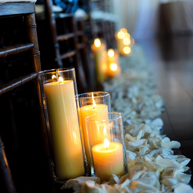 Rose petals lined both sides of the aisle with lit candles in glass vases set next to the chiavari chairs.