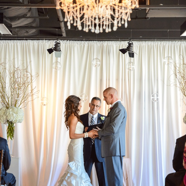 Ivory curtains with hanging lit glass balls created a gorgeous backdrop for the indoor ceremony.