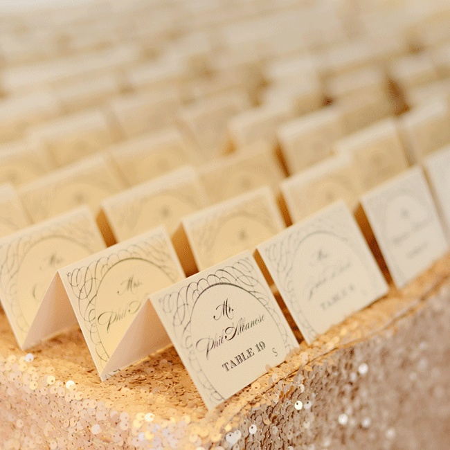 The cream escort cards shared the same script font as the rest of the stationery and were set on a gold sequin table cloth.