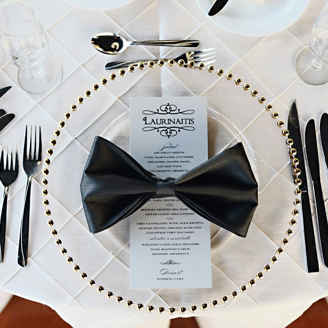 Sleek black napkins were folded into elegant bow-ties and set with the polished menu cards on gold beaded glass chargers
