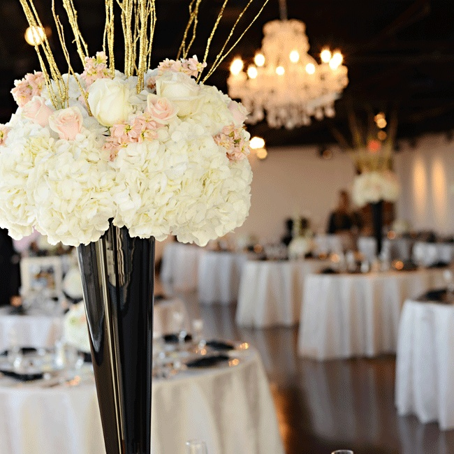 Gold glitter branches created height by emerging from the lush white floral arrangements in contrasting black trumpet vases.