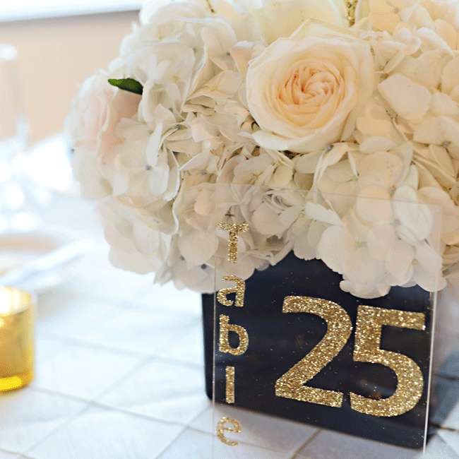Glitzy gold numbers were painted on clear signs to create contemporary table numbers.