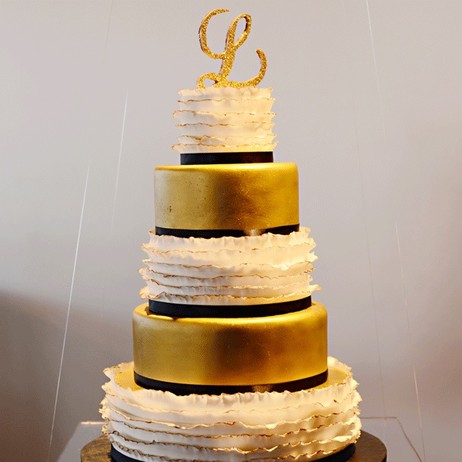 The reception's focal point was a suspended cake that featured five alternating tiers of solid gold and gold-tipped white ruffles, hanging from fishing wire on a sheet of Plexiglass.