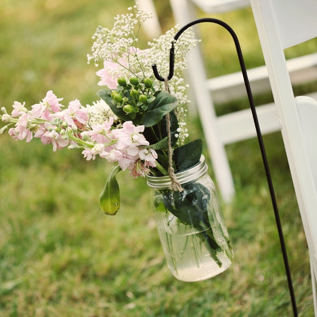 Clear mason jars filled with wildflowers from the family's garden hung from black shepherd's hooks lining the aisle.