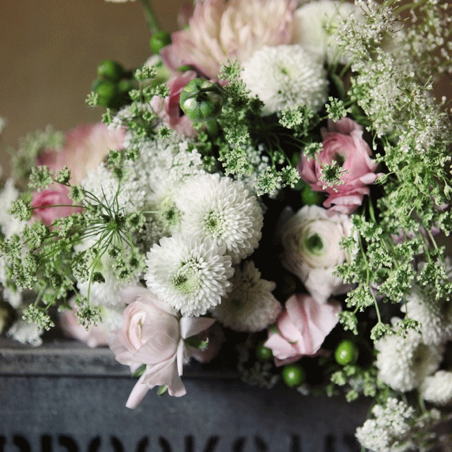 Button poms, ranunculuses, berries and Queen Anne's Lace created a stunning arrangement in a vintage crate.