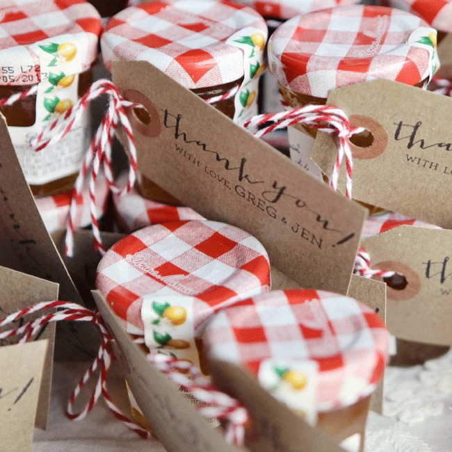Mini Bonne Maman fruit preserves favors with custom thank you cards tied on with baker's twine were displayed in antique soda crates.