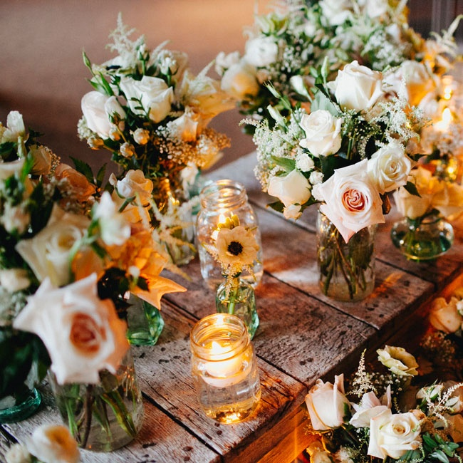Lush bouquets of pale roses and Queen Anne's Lace filled rustic mason jars.