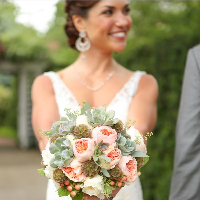 Jamison carried a vintage bouquet of light pink and white ranunculuses, lamb's ears and pops of coral berries.