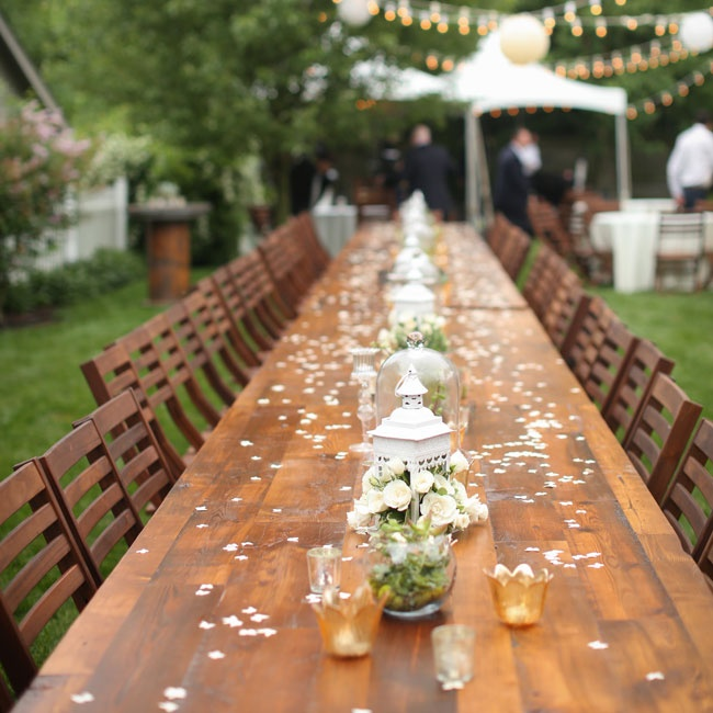 Long farm tables, surrounded by dark wood chairs and set with vintage birdcages flowing with flowers, filled the couple's backyard.