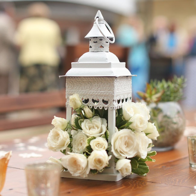 Lovely vintage centerpieces filled with lush white roses created romantic centerpieces for the backyard reception.