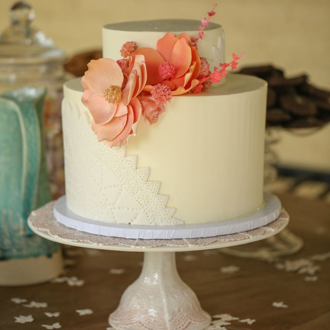 The couple served a small two-tier fondant wedding cake adorned with detailed peach sugar flowers and lace doily detailing.