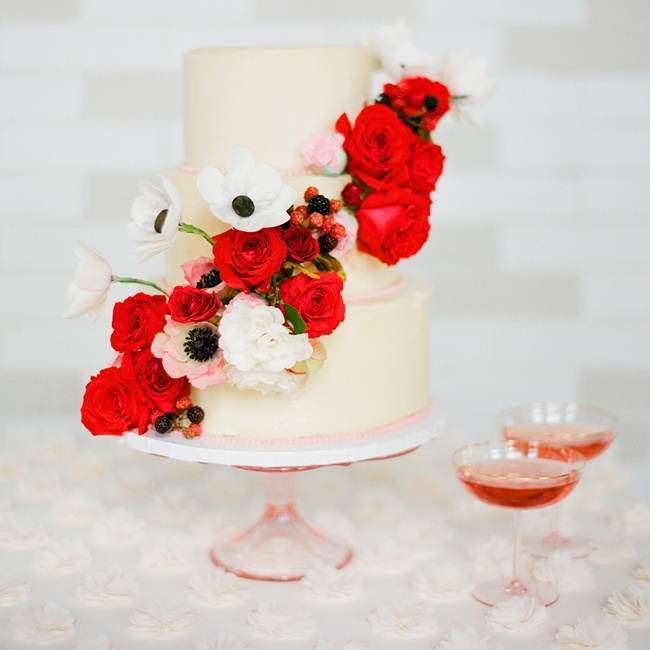 Step up a simple buttercream cake with cascading florals. A fresh-from-the-garden mix of blooms and berries keep a classic design from feeling fussy, while a modern stand and retro coupes lend sophistication.