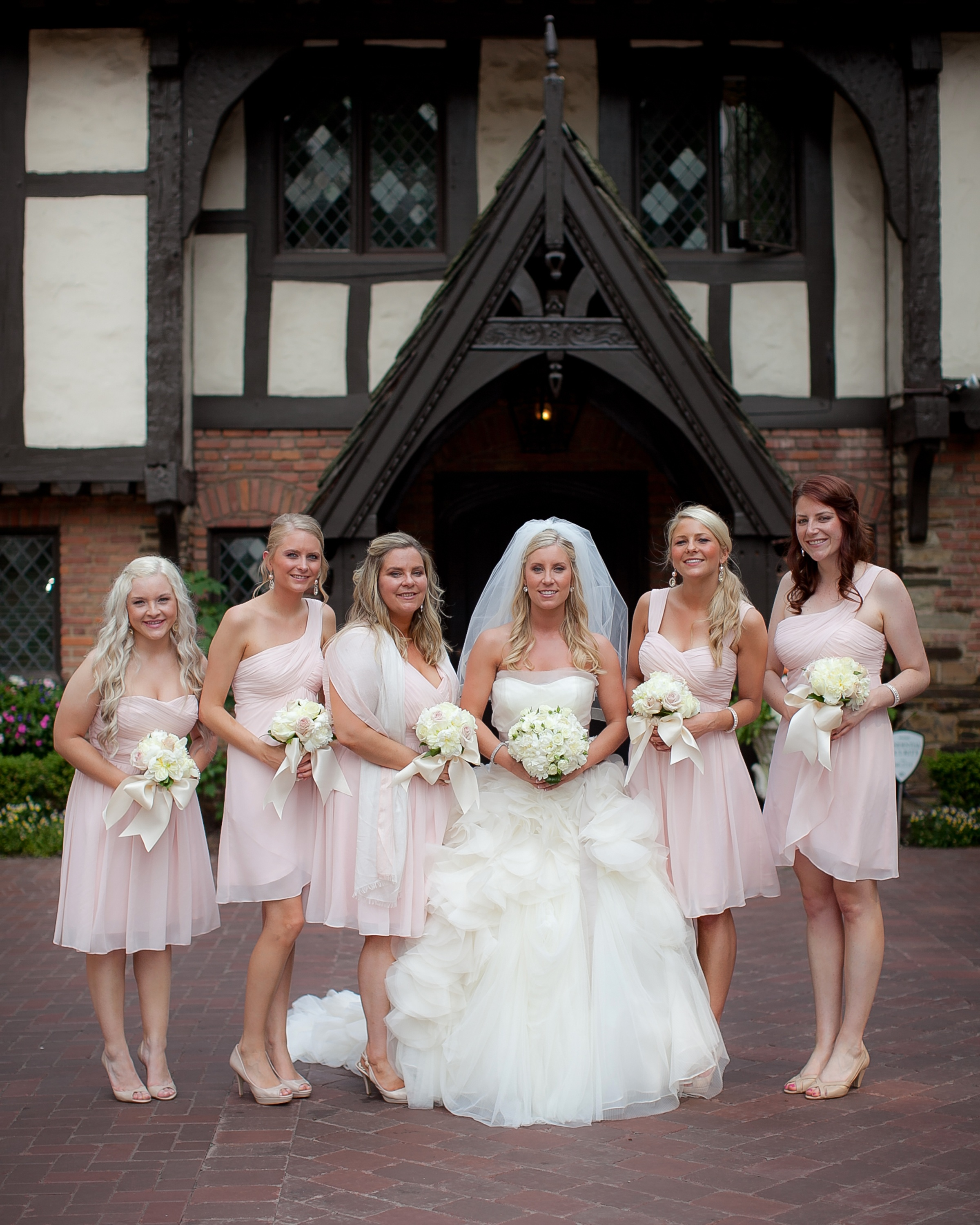 The elegant bridal party wore mixed petal pink Bill Levkoff dresses from Brides by Demetrios.