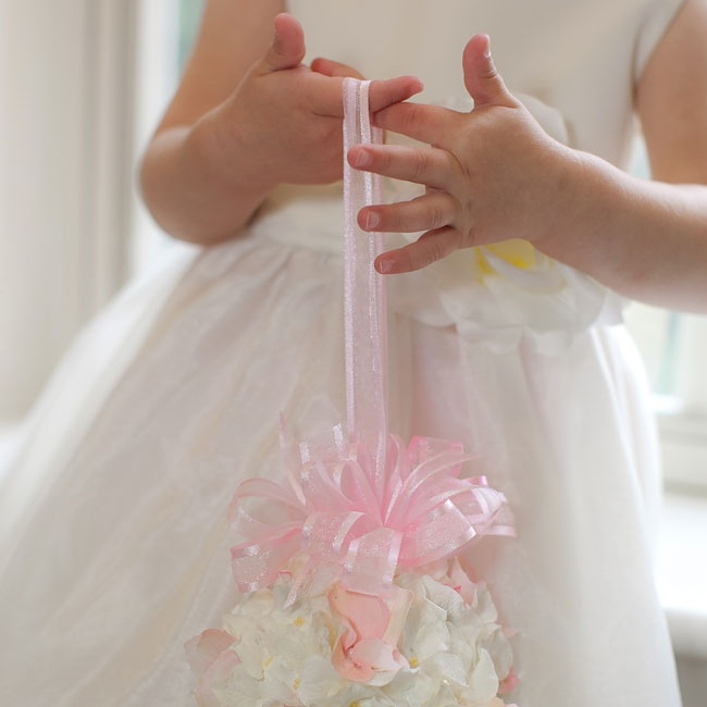 The adorable flower girl carried a soft white pomander finished with a delicate pink ribbon.