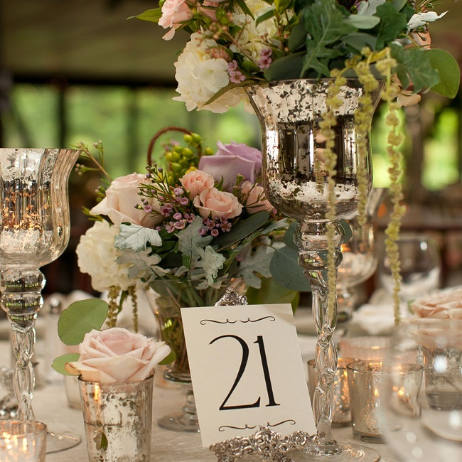 Ornate silver cardholders displayed the simple table numbers.