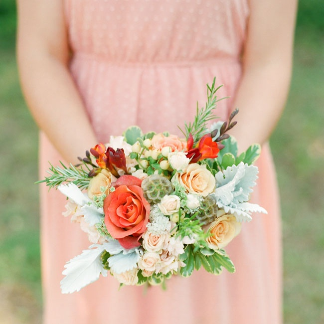 The lively coral bridesmaid bouquets were made from roses, hypericum berries, Queen Anne's Lace, variegated pittosporum, freesia, and rosemary.