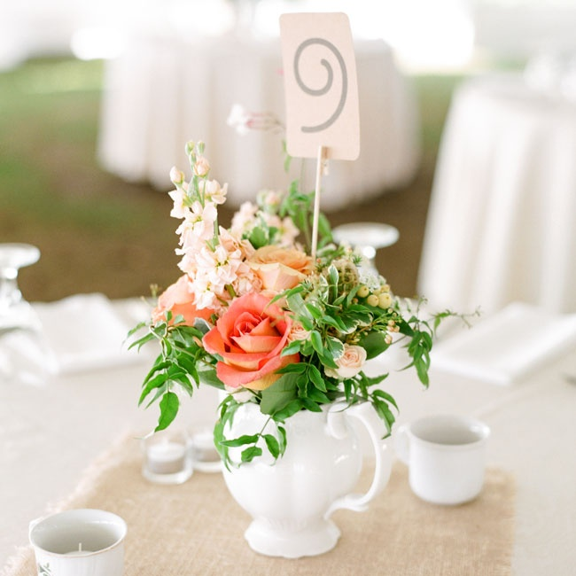 The garden centerpieces consisted of various vases and pitchers on a burlap square filled with peach and coral flowers.  A whimsical table number designed by the bride, and matching the rest of the stationery, added height to the simple tablescape.