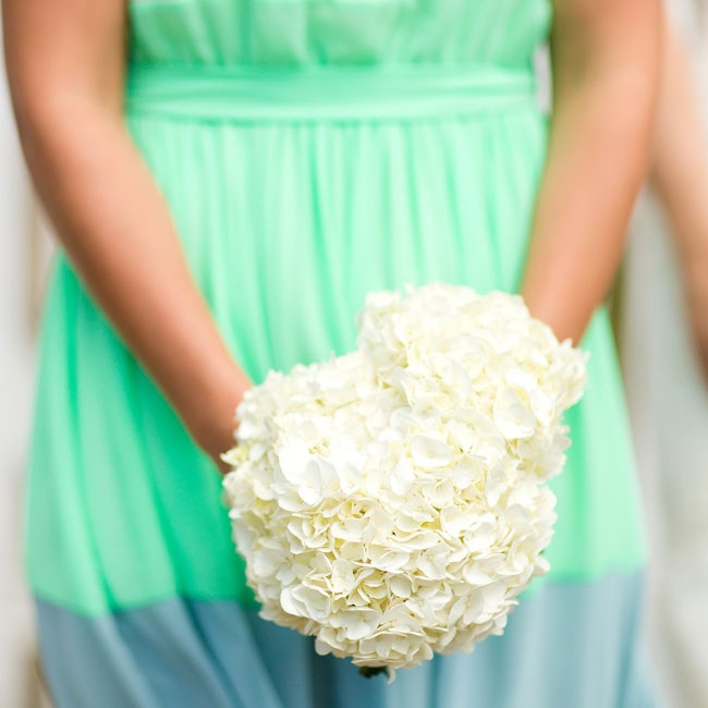 The day of the wedding a bridesmaid bundled store-bought hydrangeas, creating simple white bouquets.