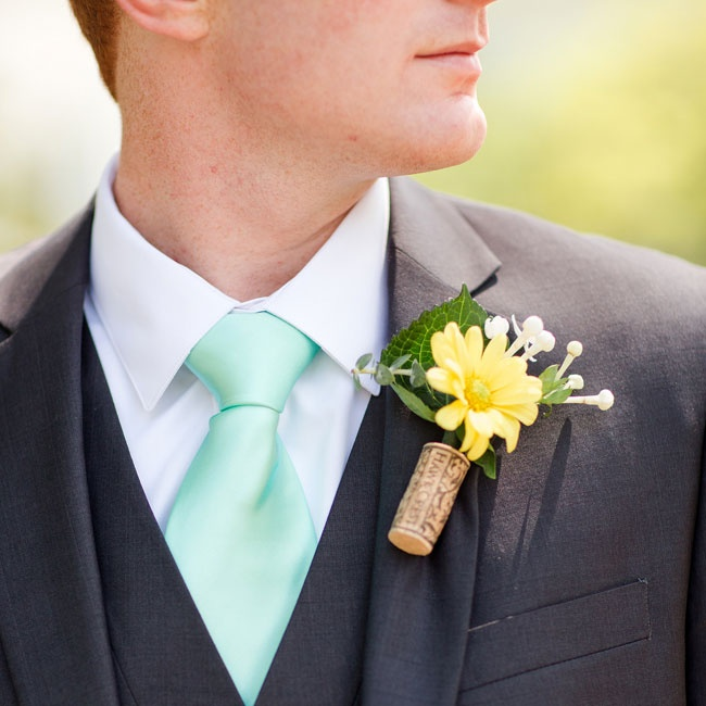 The DIY yellow daisy boutonnieres were made by a bridesmaids on the day of the wedding from Trader Joe's flowers using corks, which complemented the reception's wine bottle centerpieces.