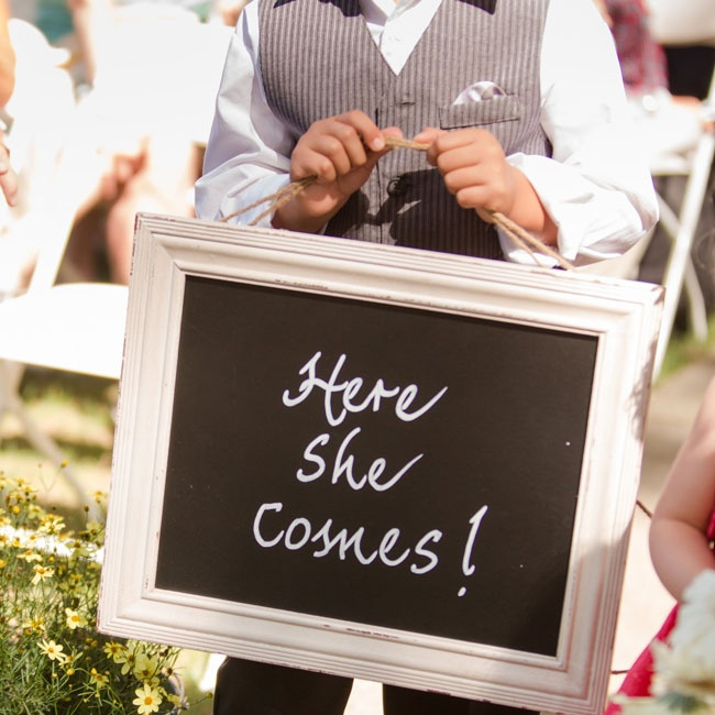 The ring bearer carried a chalkboard sign and wore a gray vest and pants to match the groomsmen.