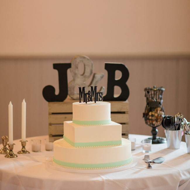 Jenna and Brendan's simple buttercream cake had alternating round and square tiers, all trimmed with mint, and was topped with a modern black Mr. & Mrs. cake topper.