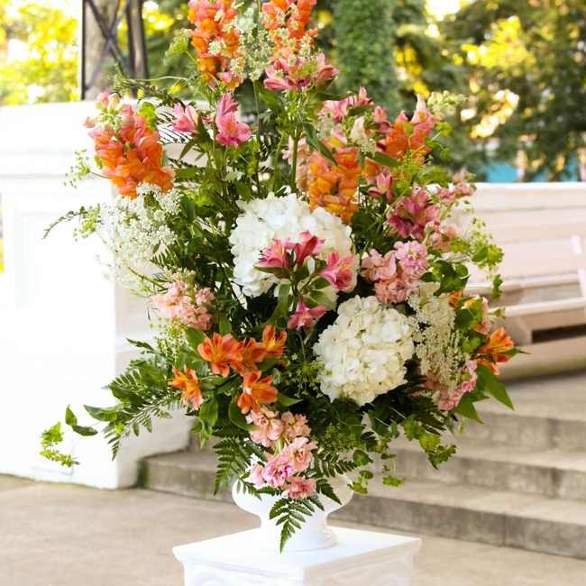 Large floral arrangements of bright orange stock, orange and pink Peruvian lilies and white hydrangeas made for stunning ceremony decor.