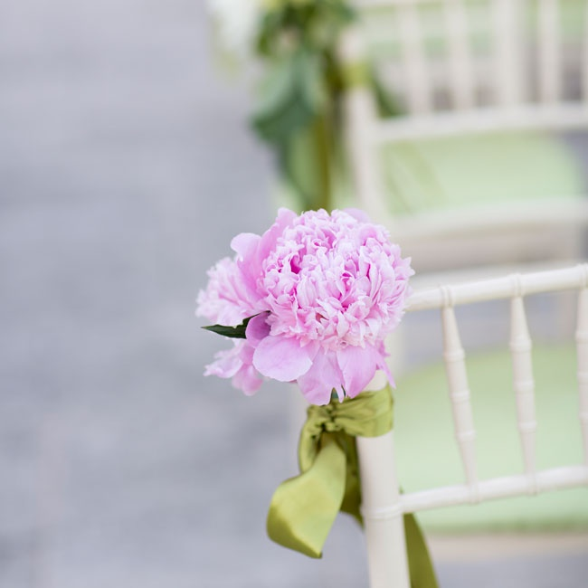 Stunning pink peonies and green satin ribbon aisle markers decorated the white chiavari chairs.