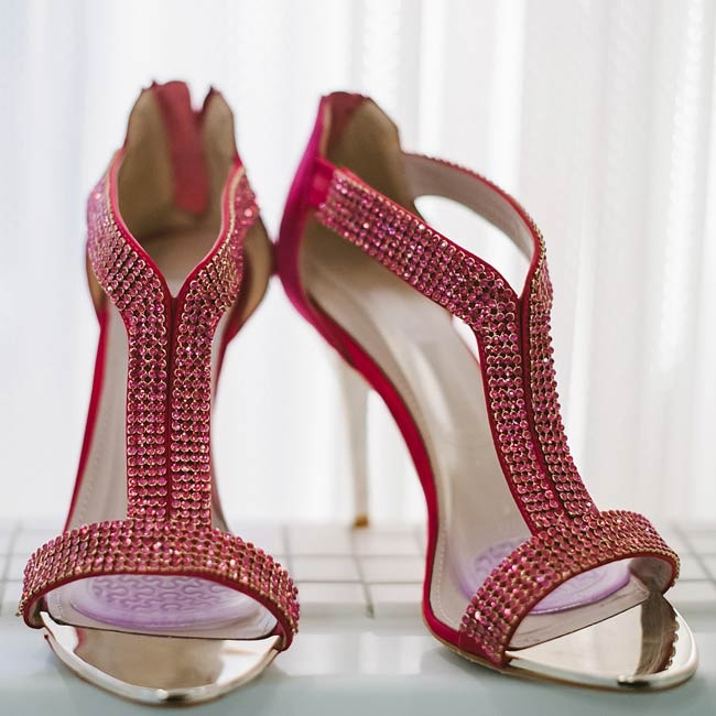 The bride wore embellished red heels by Glint as a pop of vibrant color to complement her bridesmaids' deep purple dresses.