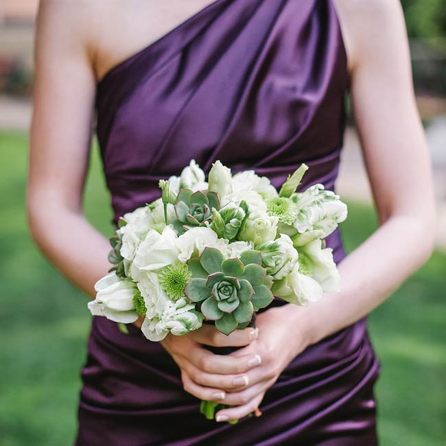 Bridesmaids held white and green bouquets featuring succulents and fresh roses in contrast to the deep purple of their dresses.