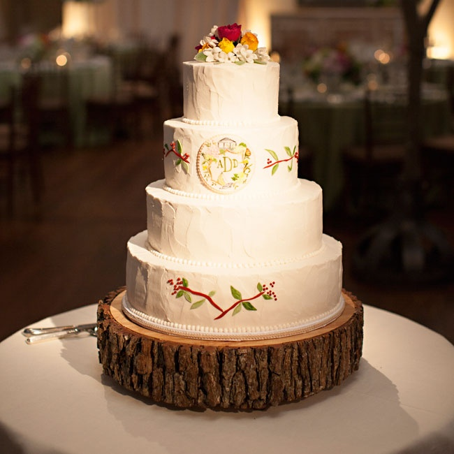 The rustic four-tier buttercream cake featured a watercolor design matching the stationary, a tree bark cake stand and was topped with a bouquet of fresh flowers.