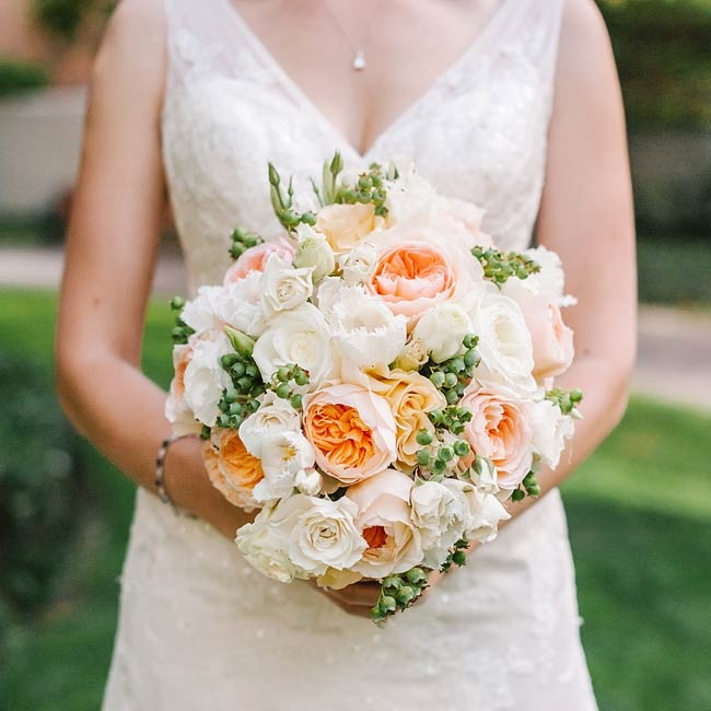 In tribute to her father, Adrienne included unripened blueberries in all of her wedding party bouquets. Her bridal bouquet also included pale orange peonies and white roses.
