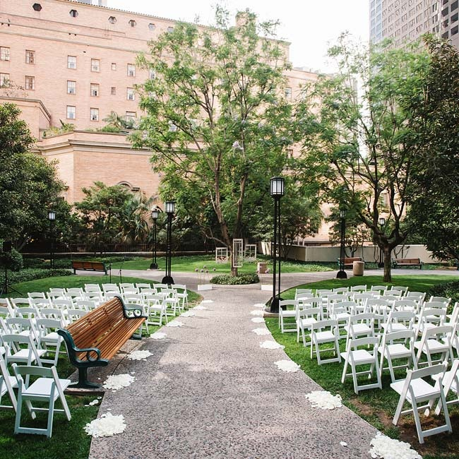 The couple exchanged vows between light posts at Cafe Pinot's Maguire Gardens. Loose flower petals marked the aisles at the outdoor ceremony site.
