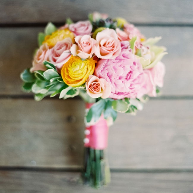 Lizzie's soft bouquet consisted of peach spray roses, pale pink peonies, green cymbidium orchids, yellow billy balls and yellow ranunculuses.