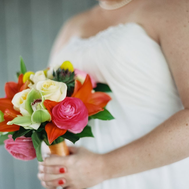 Tracy's bouquet had a tropical flair with royal sunset lilies but still complemented Lizzie's arrangement with green cymbidium orchids, hot pink garden roses, succulents, pink peonies and yellow ranunculuses.