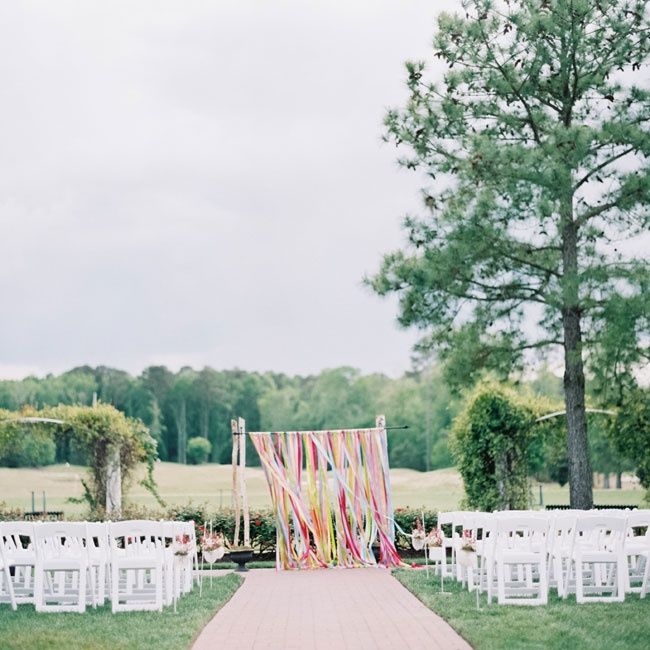 The colorful alter was created by hanging bright satin ribbons from two birch poles. The cheerful backdrop was repurposed for the reception and placed behind the dessert table.