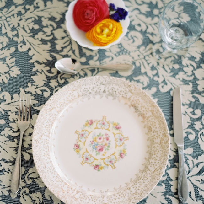 Mismatched china was set on navy linen with lace overlay for a charming vintage look. There were no table numbers or assigned seating— guests were welcome to freely move about the tables.