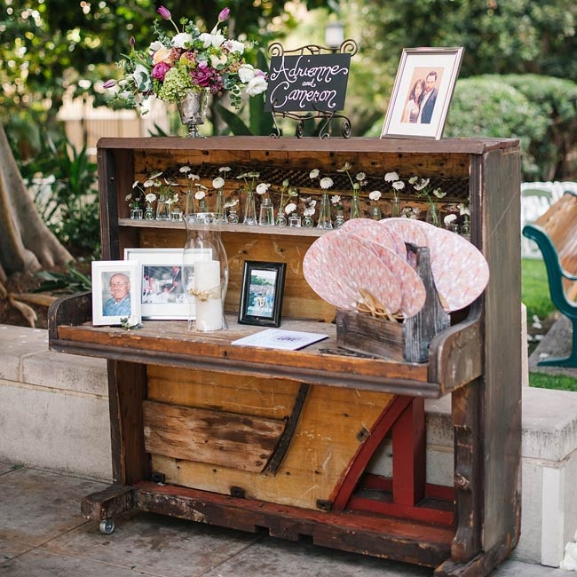 The couple paid tribute to the memory of loved ones with floral arrangements and photos displayed on an antique upright piano.